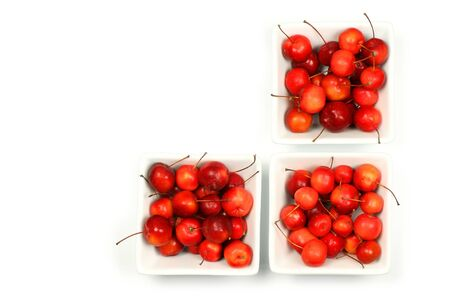 fruits of the Malus Pumila (crab apple) in white bowls on a white background  photo
