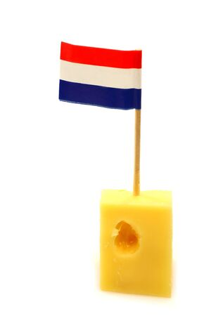 Dutch cheese with a little Dutch flag toothpick in it to pick it up on a white background  版權商用圖片