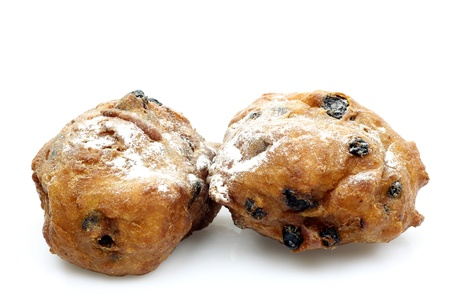powdered sugar: freshly baked traditional dutch oliebollen with currents and powdered sugar on a white background  Stock Photo