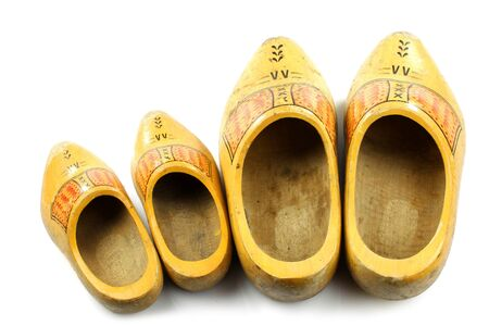 klompen: Old and young two pairs of traditional Dutch yellow wooden shoes isolated on white young and old   Stock Photo