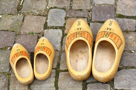 klompen: pair of traditional Dutch yellow wooden shoes on a stone footpath  Stock Photo