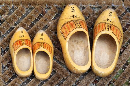 klompen: pair of traditional Dutch yellow wooden shoes outside a home on a door mat