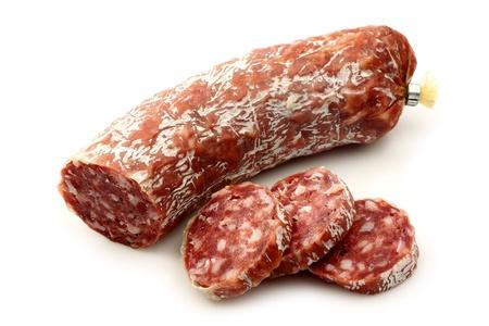 salami: salchicha picante salami italiano y rebanadas en un fondo blanco Foto de archivo