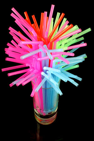 long drink glass with some water and many colored plastic straws symbolizing global water shortage on a black background  photo