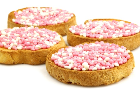 rusks with white and pink anise seed sprinkles served in Holland when a baby girl is born on a white background  photo