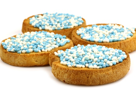 rusks with white and blue anise seed sprinkles served in Holland when a baby boy is born on a white background  photo