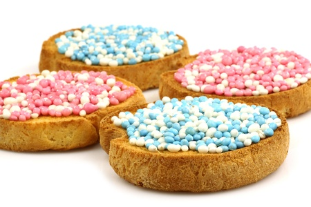 rusks with white and blue and white and pink anise seed sprinkles served in Holland when a baby boy or girl is born on a white background  photo
