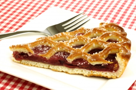 slice of decorated cherry pie called  vlaai  in Holland on a white plate  photo