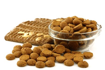 speculaas: bunch of Dutch  pepernoten  eaten at Dutch festivities around december 5th called  Sinterklaas q uot; in a glass bowl with some pieces of speculaas on a white background