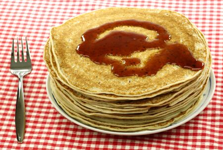flapjacks: a plate with stacked freshly baked pancakes with a fork on a checkered red and white table cloth