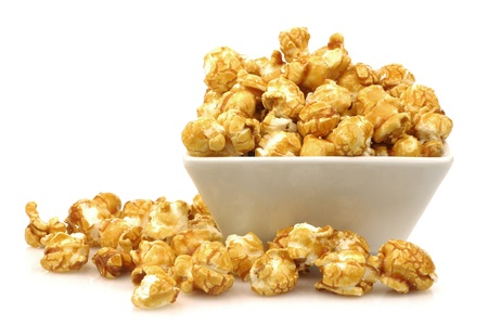 popcorn kernel: pieces of caramel popcorn in a bowl on a white background