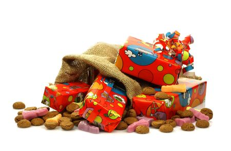colorful  Sinterklaas  presents in a burlap sack with some ginger nuts and candy on a white background