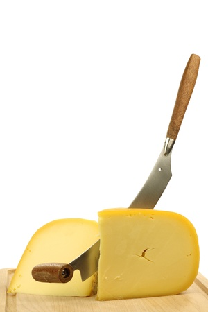 traditional Gouda cheese pieces with a cheese cutter on a cutting board  版權商用圖片