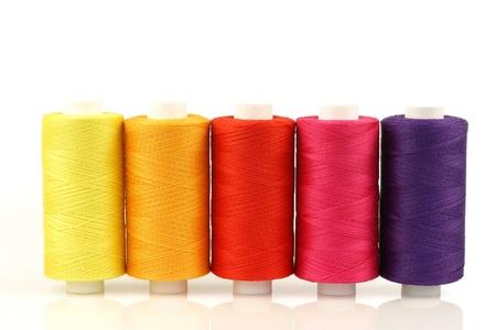 hilo rojo: colorido husos de hilado en un fondo blanco Foto de archivo