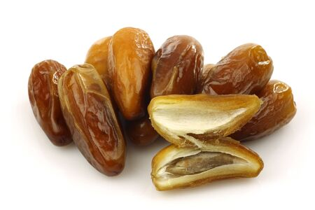 dates fruit: bunch of dried dates and an opened one on a white background  Stock Photo