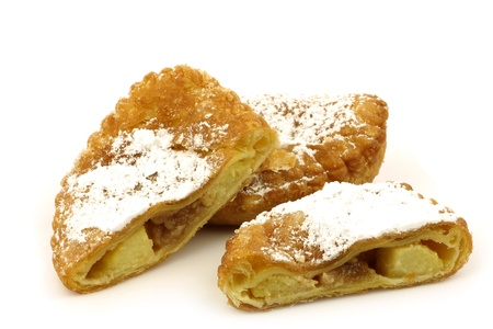 year's eve: traditional pastry from Holland eaten at new year s eve called  applebeignet  with powdered sugar on a white background
