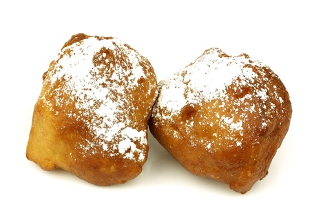 year's eve: traditional pastry from Holland eaten at new year s eve called  oliebollen with powdered sugar on a white background  Stock Photo
