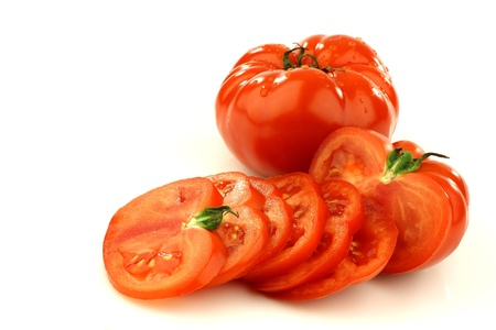 sliced beef tomato and a whole one on a white background Stock Photo - 15487531