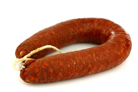 whole fresh Spanish chorizo sausage with a rope on a white background