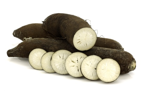 three long black winter radishes  Raphanus sativus subsp  niger  and a cut one on a white background  Banque d'images