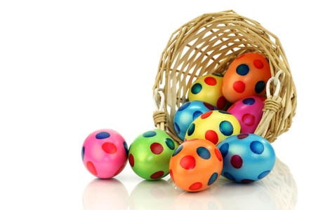 interleaved: colorful easter eggs coming from a wicker basket on a white background  Stock Photo