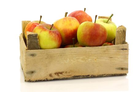 fresh red and yellow apples coming from a wooden box on a white background  photo