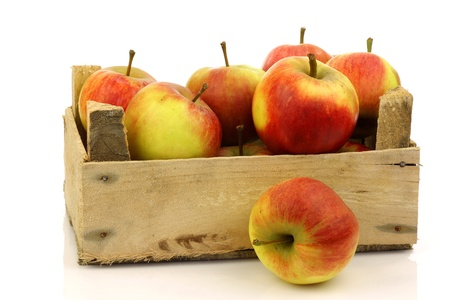 fresh red and yellow apples coming from a wooden box on a white background