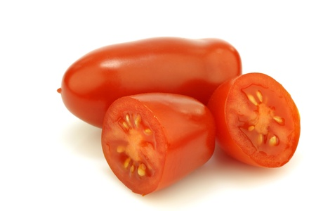 one whole italian tomato and two halves on a white background Stock Photo - 15050237