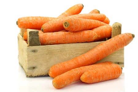 fresh winter carrots in and around a wooden box on a white background