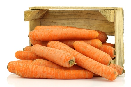 fresh winter carrots coming from a wooden box on a white background  Stock Photo