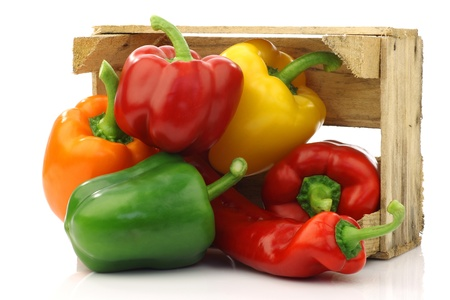 colorful mix of paprika s capsicum  in a wooden box on a white background