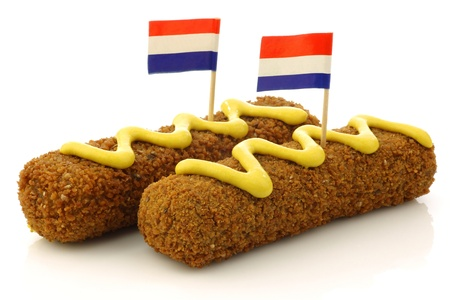 Two Dutch snacks called  kroket  with mustard and Dutch flag toothpicks on a white background
