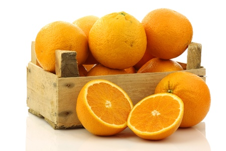 fresh oranges and two halves in a wooden box on a white background  Stock Photo