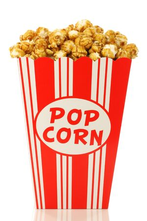 caramel popcorn in a decorative paper popcorn cup on a white background  photo