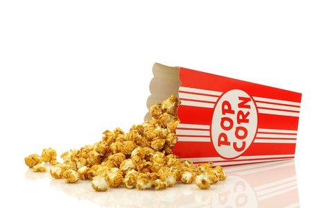 corn kernel: caramel popcorn in a decorative paper popcorn cup on a white background