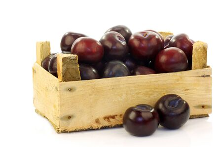 fresh plums in a wooden crate on a white background