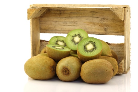 green kiwi fruit and some cut ones in a wooden box on a white background  photo