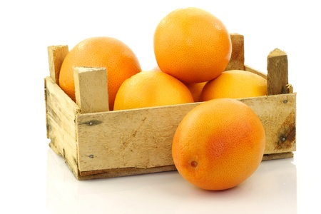 produce sections: fresh red grapefruits in a wooden box on a white background  Stock Photo