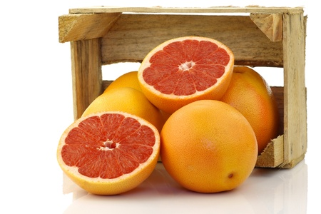 fresh red grapefruits in a wooden box on a white background  photo