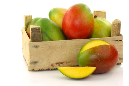 crate: fresh mango fruit and a cut one in a wooden box on a white background  Stock Photo