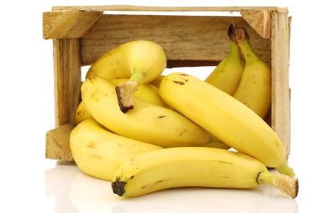 fresh bananas in a wooden crate on a white background