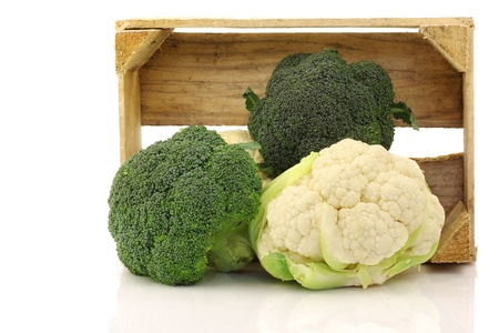 Fresh cauliflower and broccoli in a wooden crate on a white background  photo