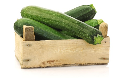 fresh zucchini s  Cucurbita pepo  in a wooden box on a white background