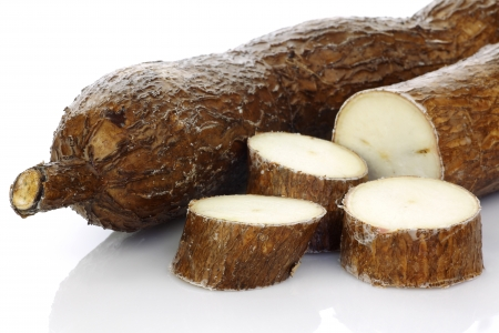 cassava: one whole and a cut cassava on a white background