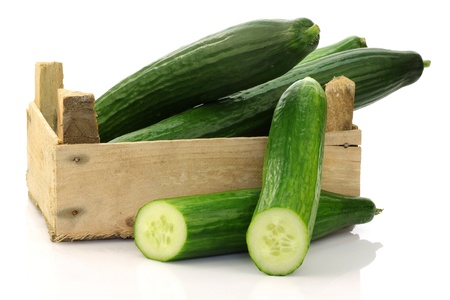 fresh cucumbers and a cut one in a wooden box on a white background  Stock Photo