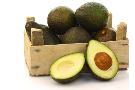 avocado: fresco e avocado maturo s e un taglio in una cassa di legno su uno sfondo bianco