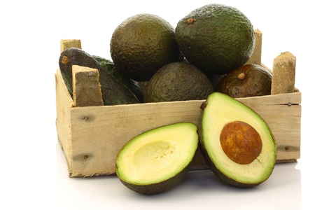 fresh and ripe avocado s and a cut one in a wooden crate on a white background