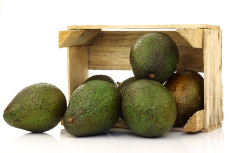 fresh and ripe avocado s in a wooden crate on a white background  Stock Photo