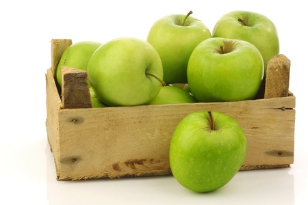 granny smith: freshly harvested  Granny Smith  apples in a wooden crate on a white background  Stock Photo