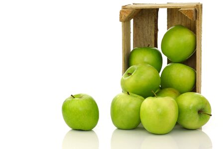 freshly harvested  Granny Smith  apples in a wooden crate on a white background  photo